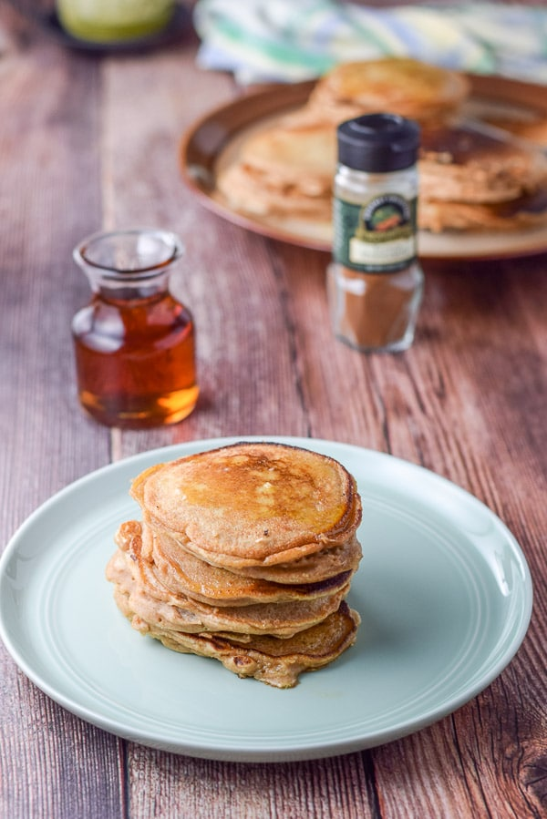 A green plate with 5 pancakes stacked on it. There is cinnamon, maple syrup and more pancakes in the background