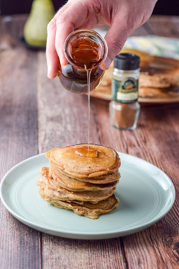 Maple syrup being poured onto Bena's apple pancakes