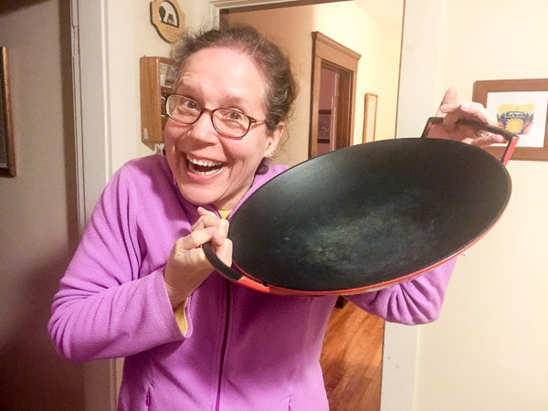 Elaine, wearing a wide, goofy smile and holding up her red Le Creuset wok, purchased at a local Savers thrift store.