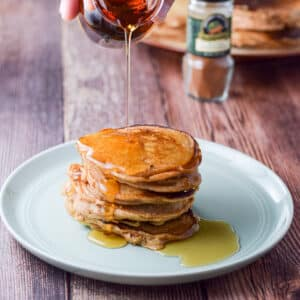 A green plate piled with pancakes and then drizzled with maple syrup - square