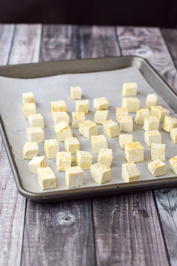 Curry coated tofu cubes on a parchment paper lined jelly roll pan