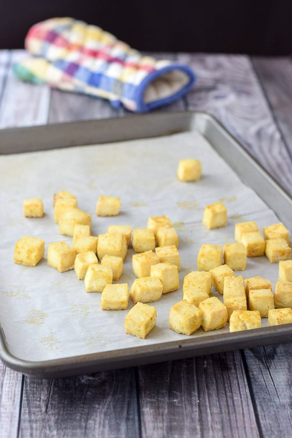 Tofu cubes baked and crispy on a jelly roll pan