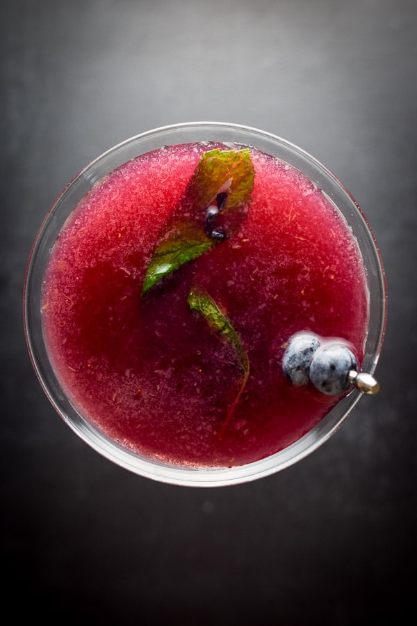 Aerial view of the blueberry cosmo with blueberries and mint leaves for garnish