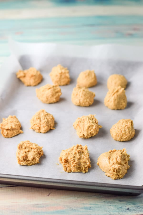 The peanut butter balls formed on a parchment paper pan