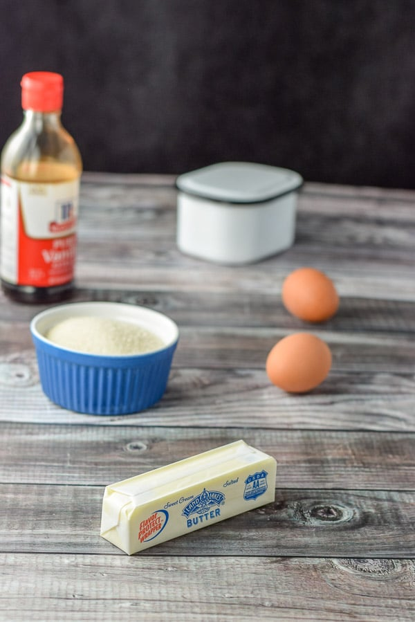 Butter, eggs, sugar, vanilla and salt on a greyish table