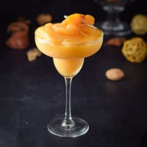 A margarita glass filled with a frozen orange cocktail with peaches speared on a pick - square