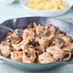 Chicken and mushrooms in the pan with a shallow bowl of pasta in the background - square