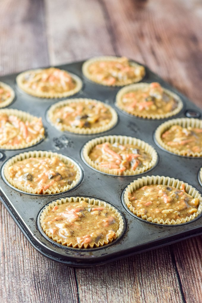 Batter in the muffin tins and on a wooden table
