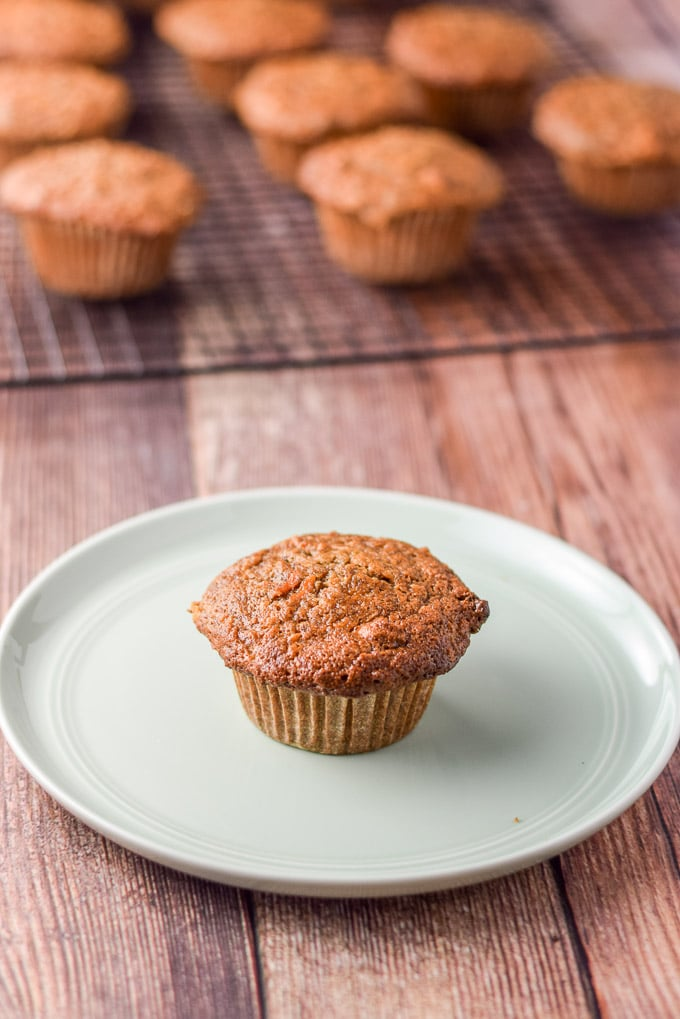 A small green plate with a muffin on it with a wire rack in the background