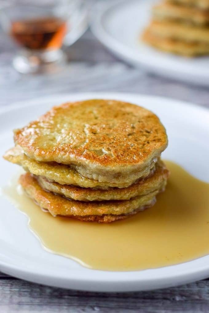 Close up of four pancakes with syrup poured on them