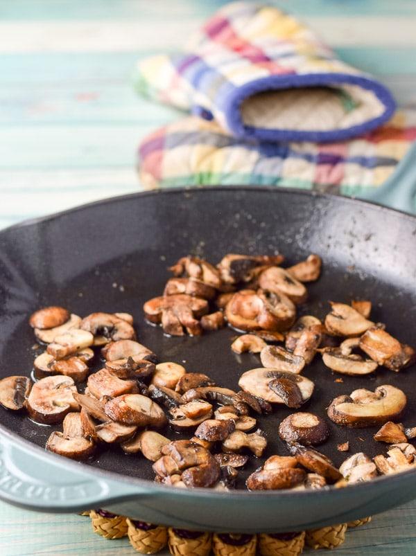 Mushrooms sautéd in a cast iron skillet
