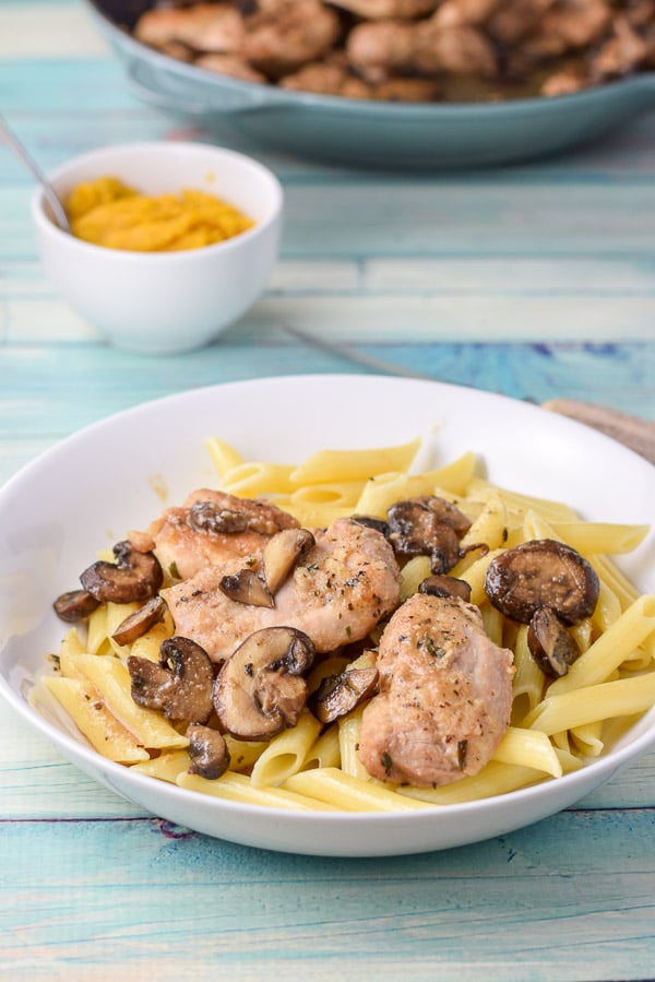 A shallow bowl of pasta with chicken and mushrooms on it