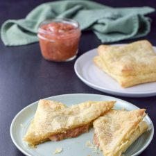 Aerial view of a baked pastry square stuffed with cream cheese and rhubarb sauce sliced in half on a plate in front and a whole baked pastry square on a plate and small jar of rhubarb sauce in back