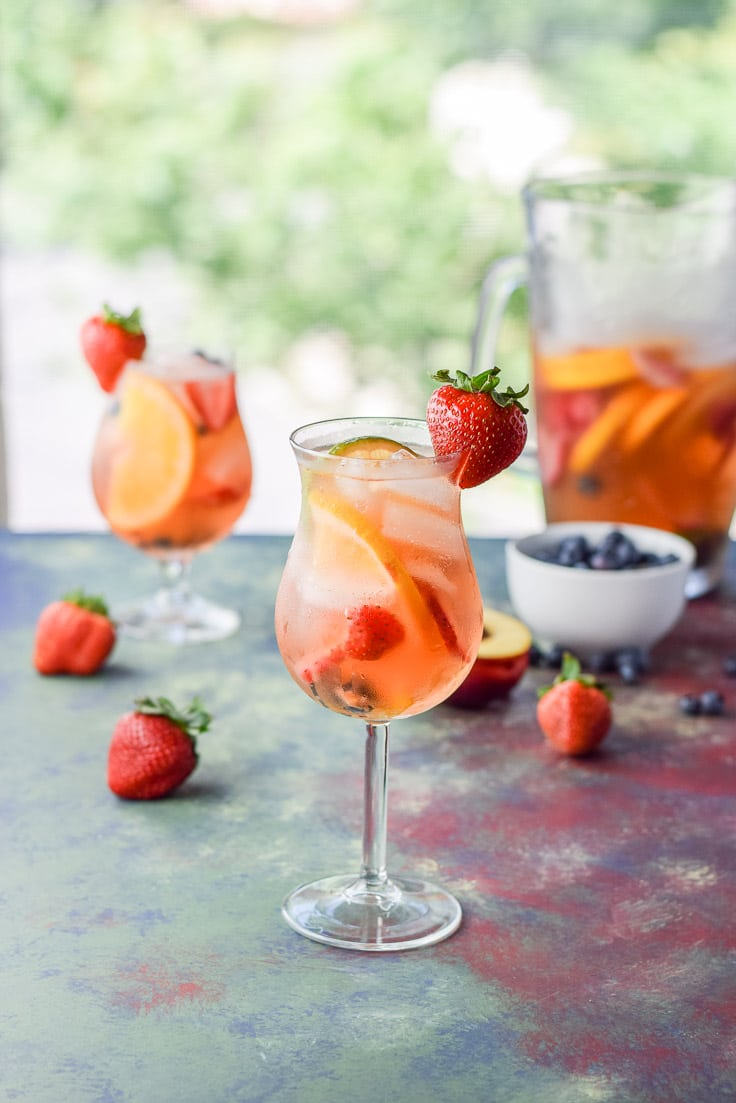 Strawberries on the side of the glasses of sangria with fruit and a pitcher in the background