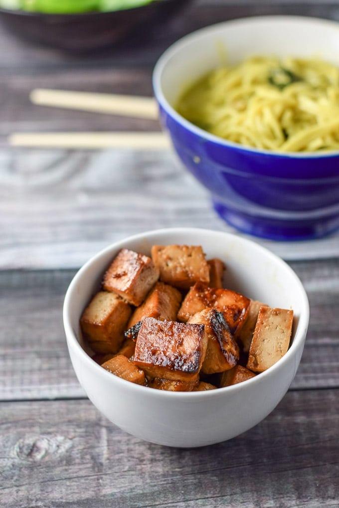 A white bowl with sautéed tofu with a bowl of noodles in the background