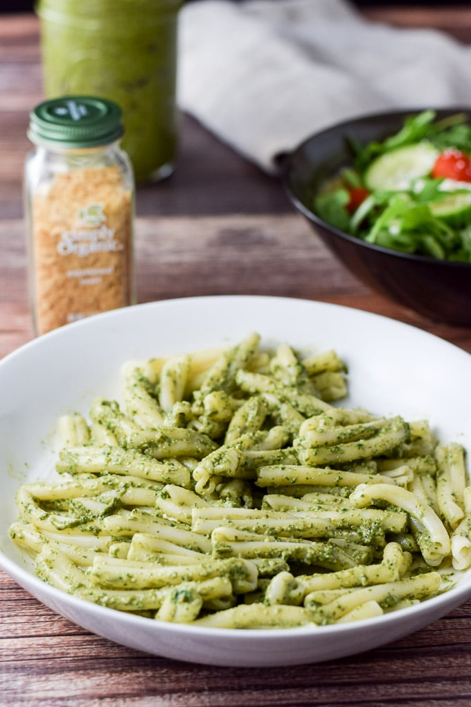 Close up of a white bowl with pesto pasta with a bottle, jar and salad in the background
