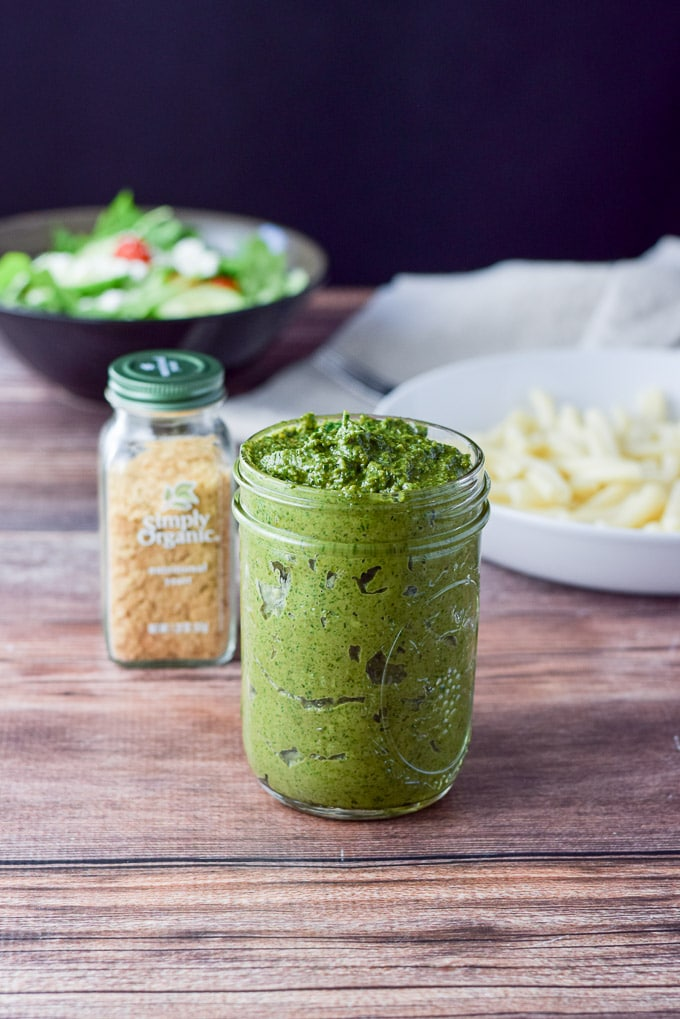 Thick pesto sauce shown in a jar, with yeast, pasta and a salad in the background