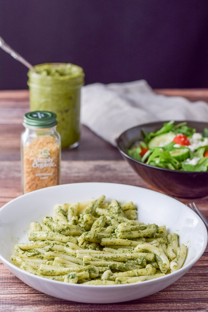 Pesto sauce mixed in with pasta with a salad in the background
