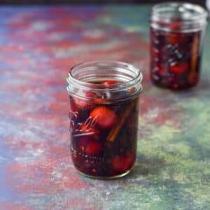 Cherries and cinnamon in bourbon in two jars on a table - square