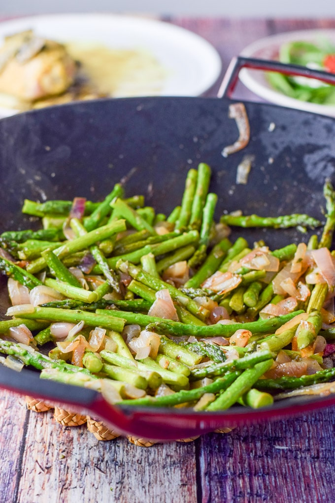 Asparagus in the wok completely cooked with a plate of chicken in the background