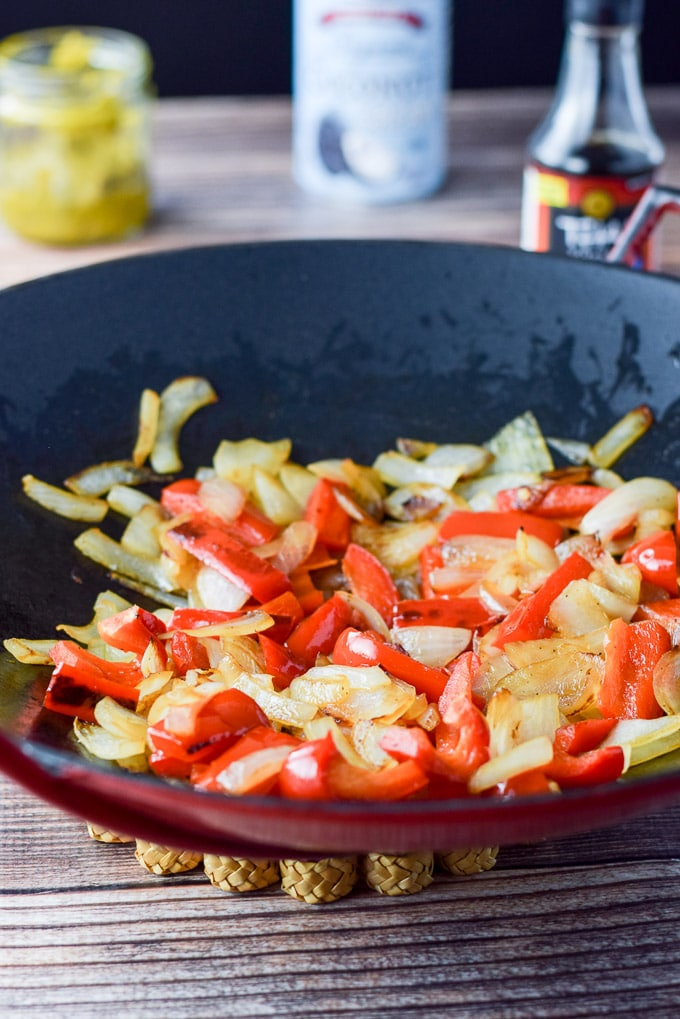 Peppers and onion sautéed for the in a cast iron wok. There is curry, coconut milk and fish sauce in the background