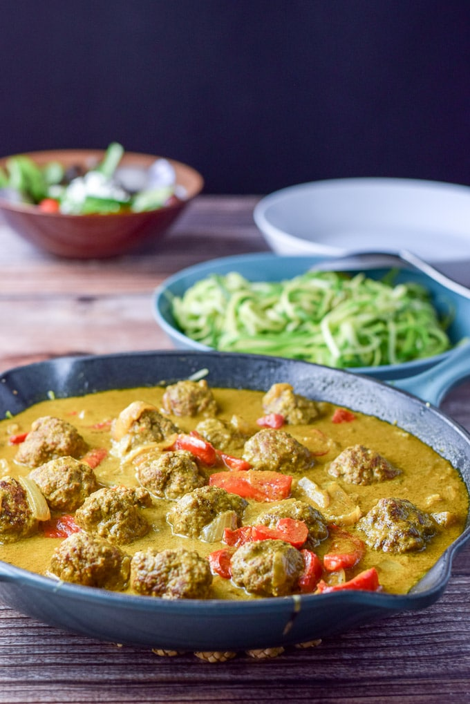 A sauté pan filled with curry sauce and meatballs. There is a bowl of zoodles and a salad in the background