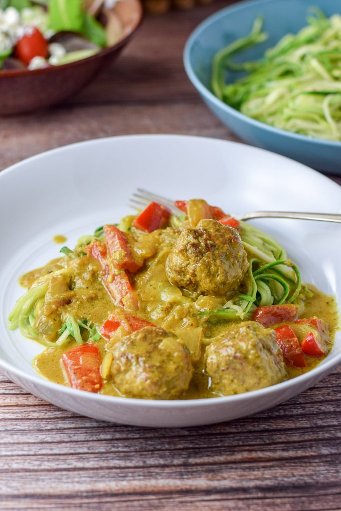 A white shallow bowl with meatballs in curry sauce over zoodles