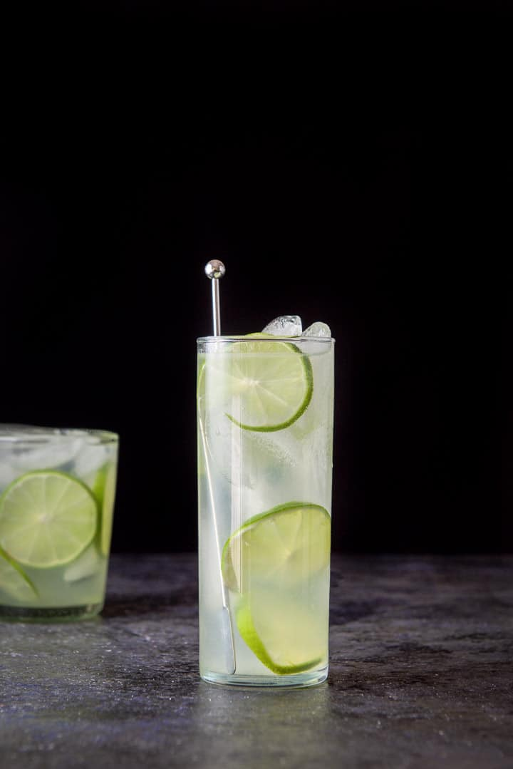 Vertical view of the tall glass filled with the lime rickey with the other glass off to the left