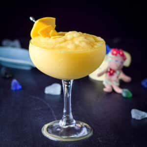 The margarita in a classic glass with mangos on a pick as garnish - square