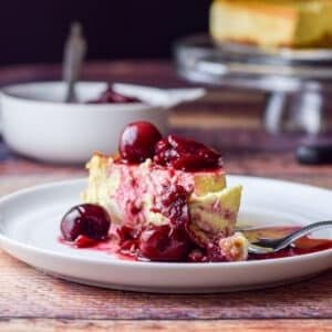 A small plate with the cheesecake covered with cherries and a fork with a bite laying on the plate - square