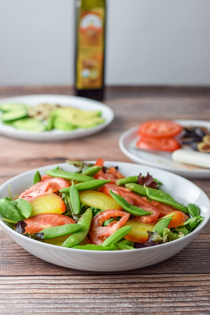 Snap peas and tomatoes are added to the salad with other ingredients in the background