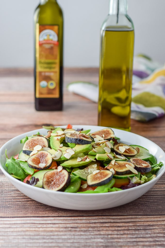 Figs and almond slices added to the salad with oil and balsamic vinegar in the background