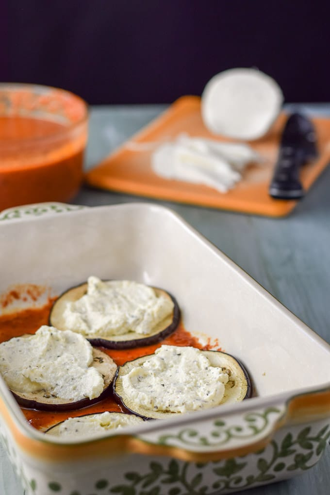 Gravy on the bottom of a baking dish, eggplant on the gravy and ricotta cheese on top of that