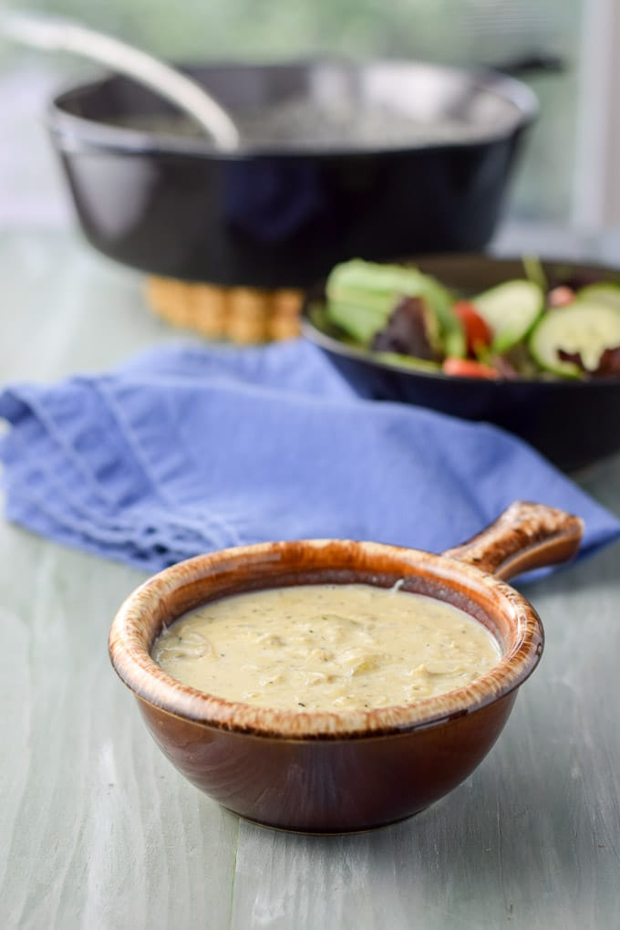 Different view of the bisque in a brown crock with a napkin, salad and pan in the background