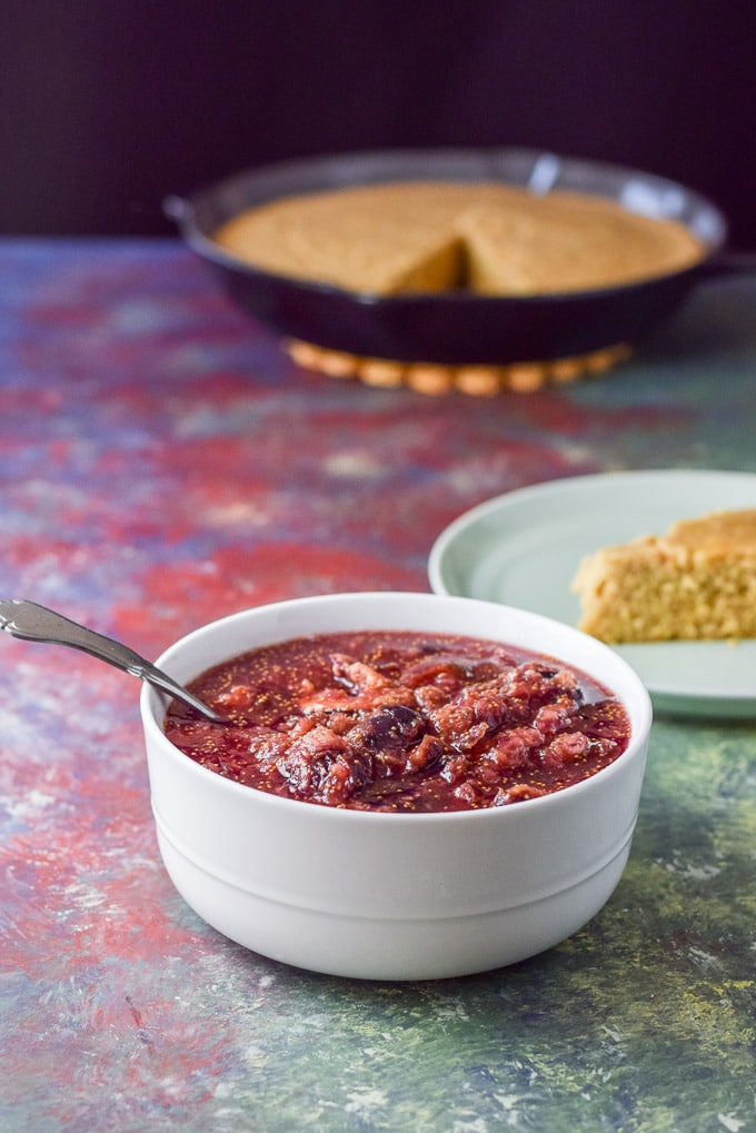 The sauce made of figs in a white bowl with some skillet of cornbread in the background