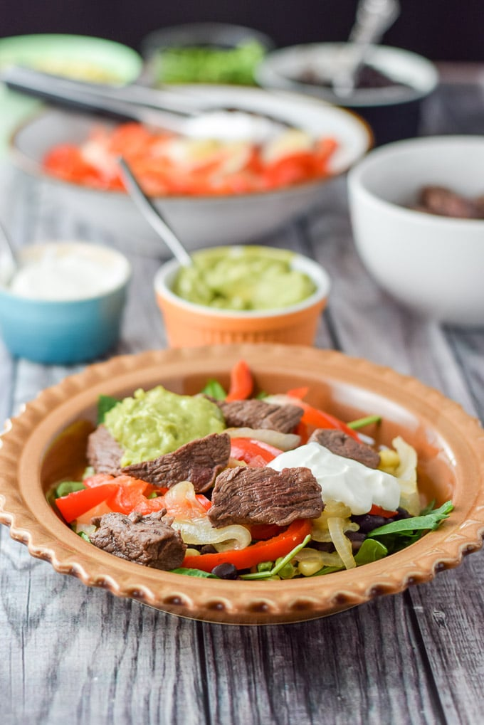 Guacamole and sour cream dolloped on the steak fajita burrito bowl
