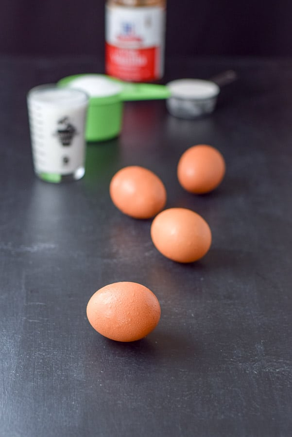 Eggs, almond milk, sugar, flour and vanilla on a black board
