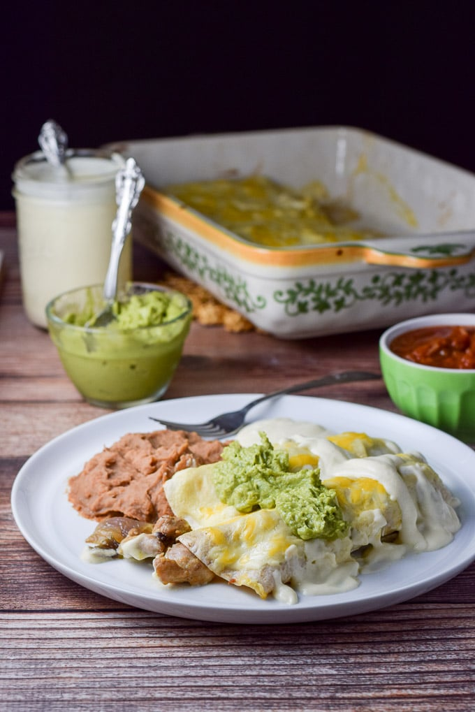 Guacamole and more sour cream sauce draped over the chicken enchiladas with white sauce ready to be eaten.