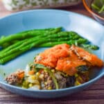 Close up of a blue bowl with the shepherds pie and asparagus in it - square