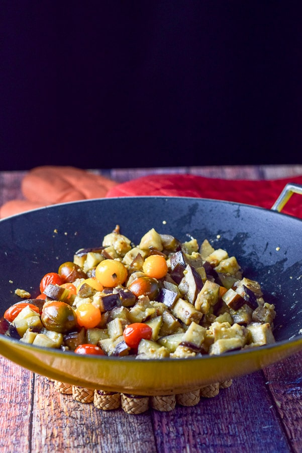 Sautéed eggplant and tomatoes in a yellow wok with two oven mitts in the background