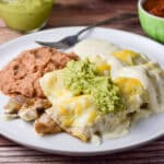 Guacamole and more sour cream sauce draped over the enchiladas with beans on the plate as well