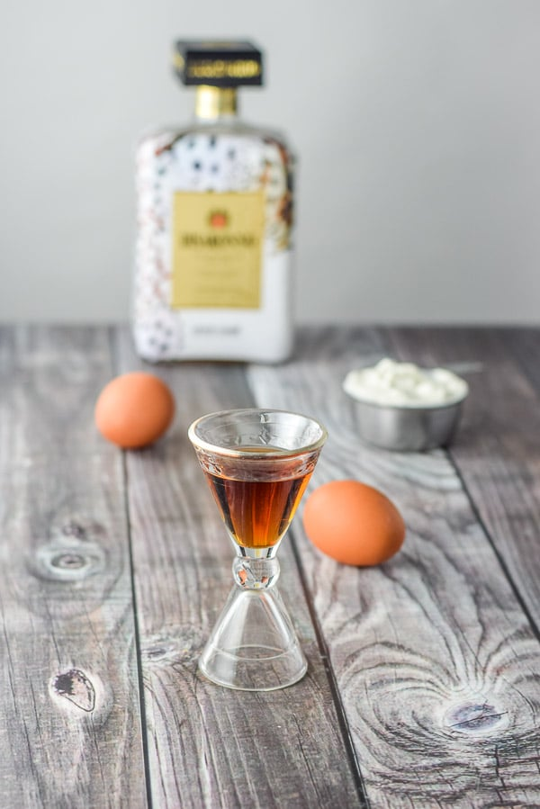 Amaretto, eggs and sour cream on a grey table