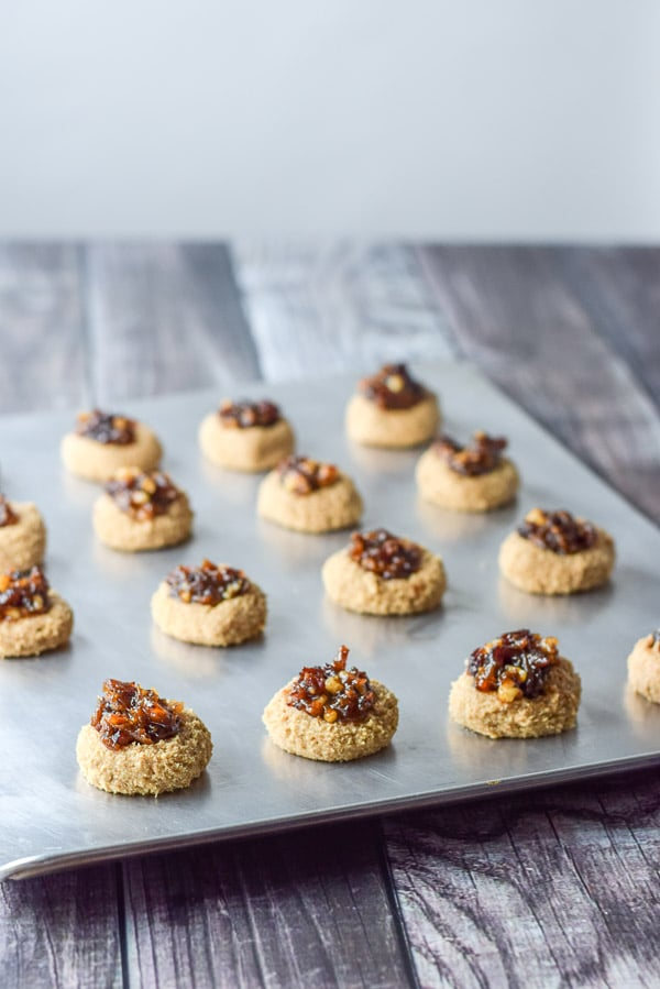 Dates and nuts put in the thumbprints on a cookie sheet