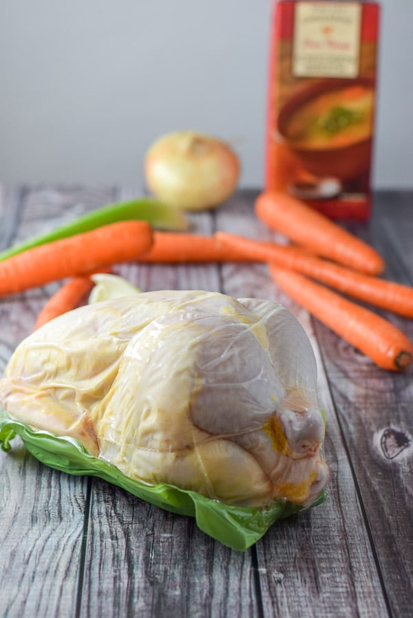 Organic whole chicken all wrapped up, carrots, celery and an onion for the chicken soup