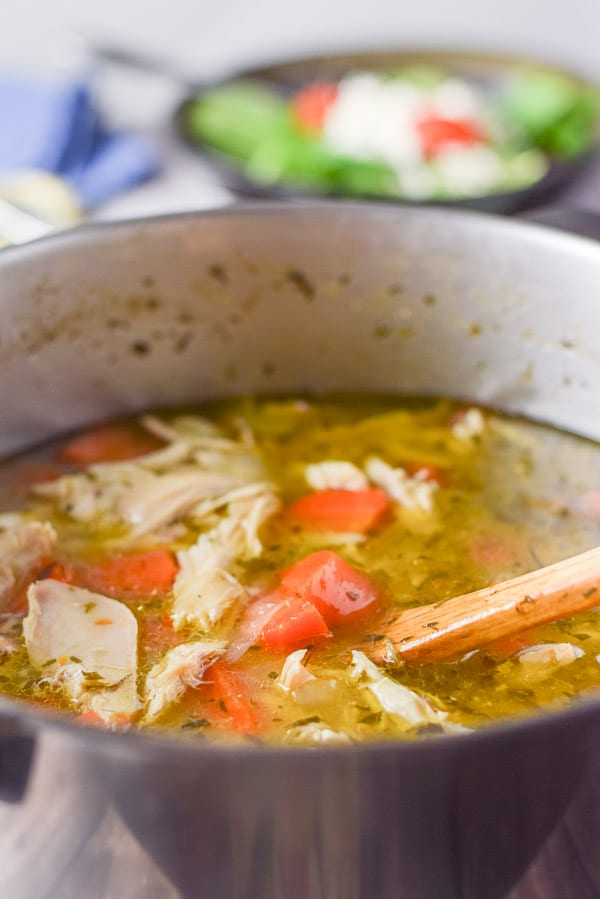 Close up of the chicken soup in the pan with a wooden spoon in it and a salad in the background
