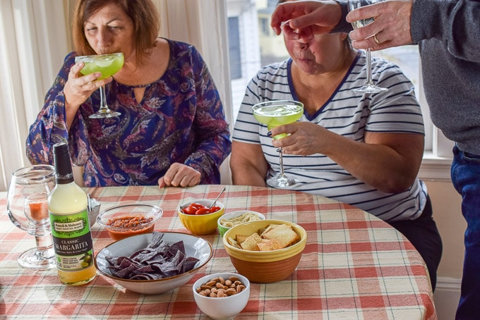 A woman sipping the margarita while the other is munching on some appetizers