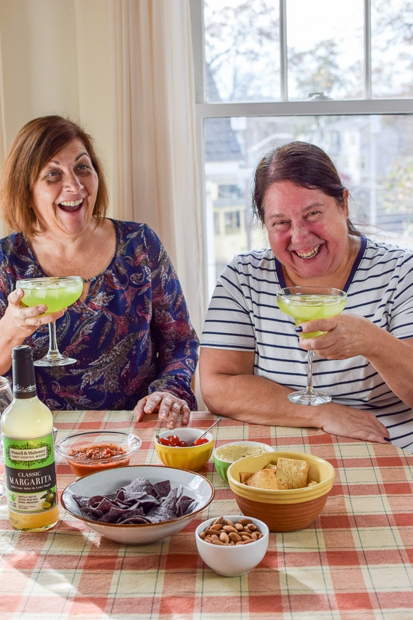 Two women laughing at a joke with the margarita in their hands