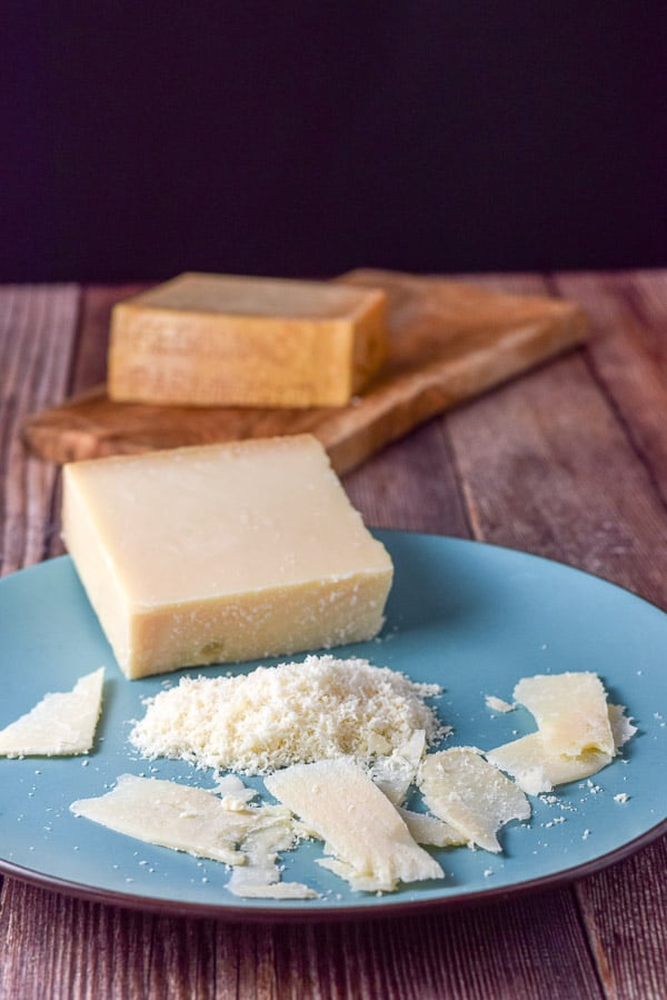 Shaved and freshly grated reggiano parmigiano cheese on a blue plate