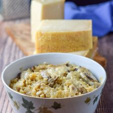 Marvelous mushroom parmesan rice casserole in a bowl with the glorious cheese behind it