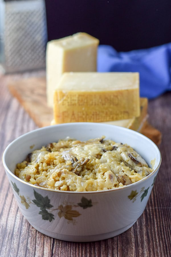 Marvelous mushroom rice casserole in a bowl with the glorious cheese behind it